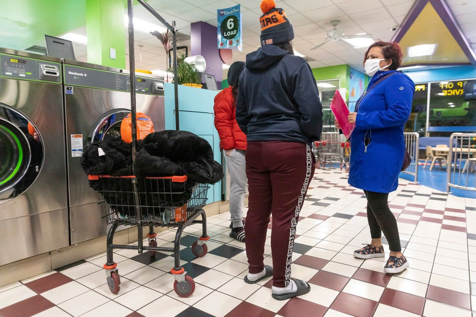 Margarita Sanchez, a promotora de salud — community health worker — with Centro San Bonifacia, conducts a survey about COVID-19 and helps answer questions for people on Jan. 15, 2021, at a laundromat in Belmont Cragin on Chicago's Northwest Side. Manuel Martinez / WBEZ News.