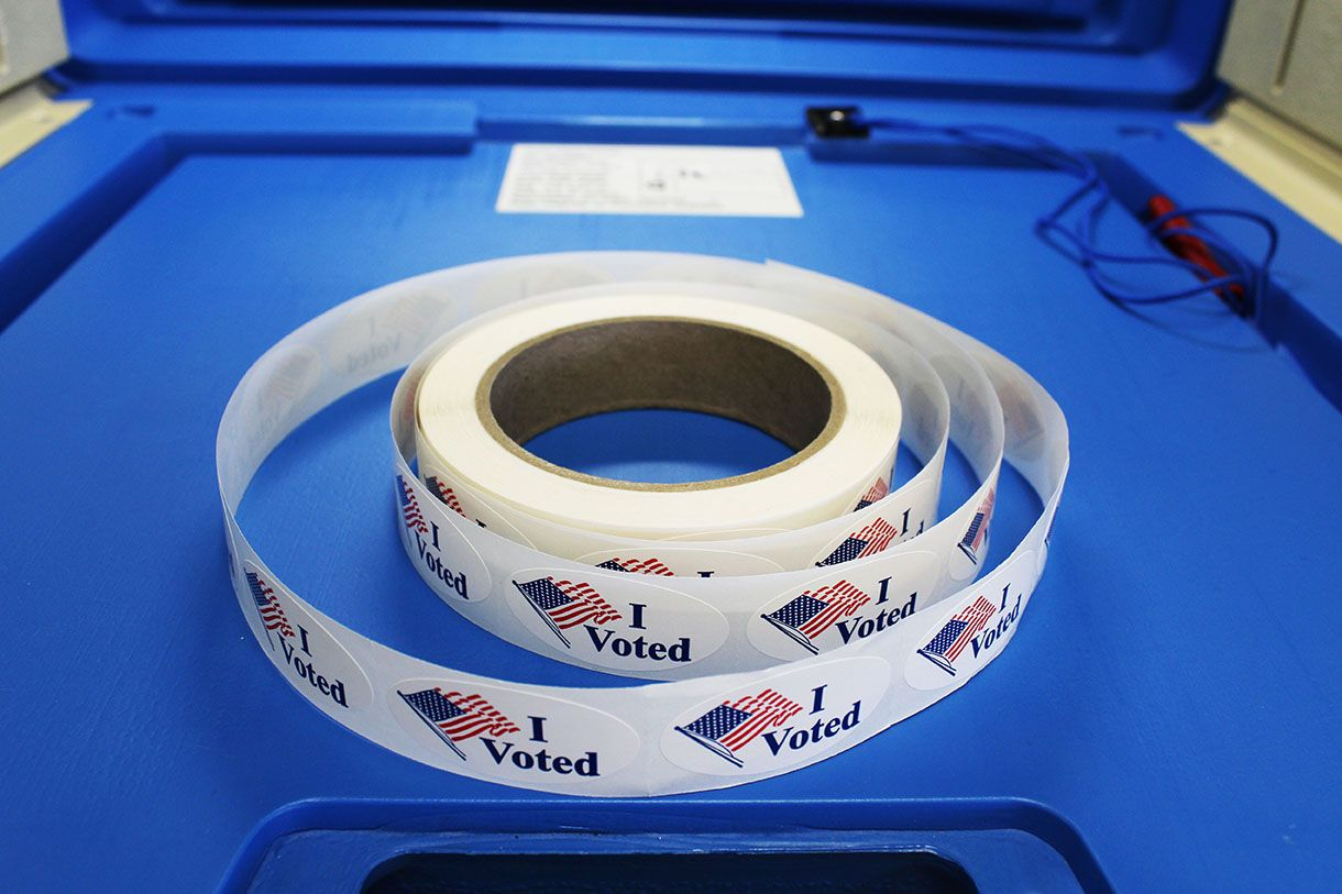 """Red white and blue """"I voted"""" stickers with American flag are on a spool of stickers placed on a voting booth platform. Image byBarbara Kalbfleisch. United States, undated."""