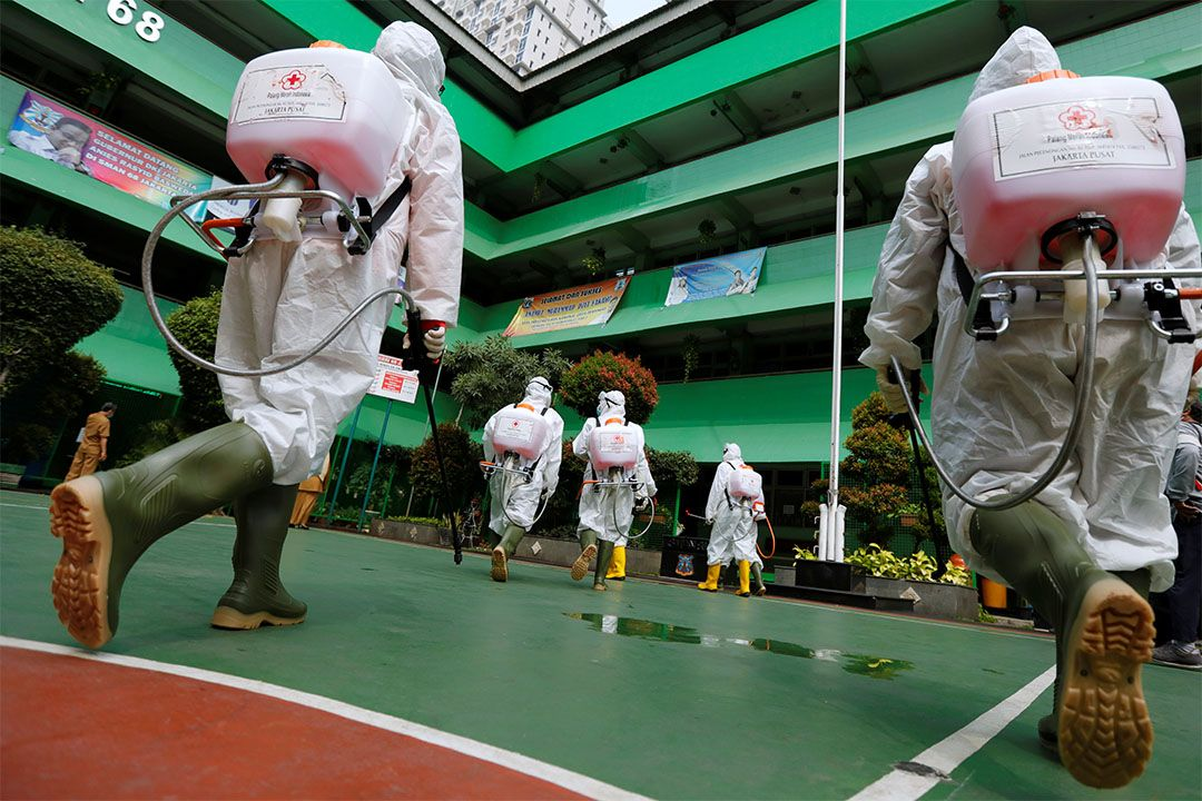 Volunteers from Indonesia's Red Cross prepare to spray disinfectant at a school closed amid the spread of coronavirus (COVID-19) in Jakarta. Image by REUTERS/Willy Kurniawan. Indonesia, 2020.