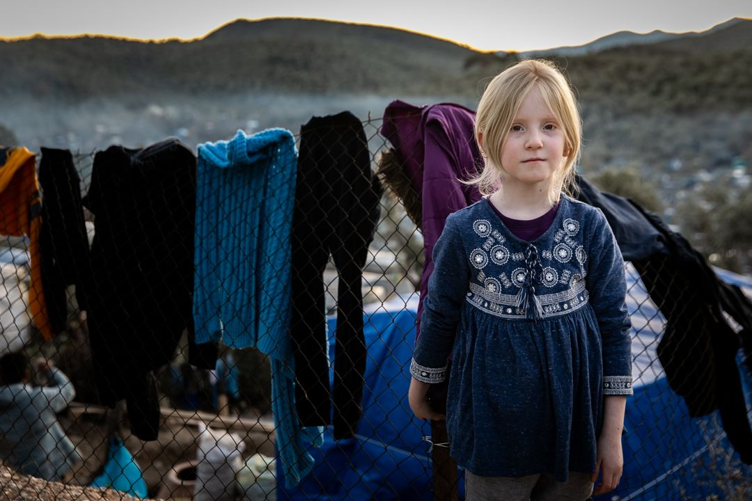 A young girl stands near the laundry she hung to dry in Moria on Lesbos on January 4, 2020. Approximately one-third of the over 20,000 people in Moria are children, and an estimated 1,500 of them are unaccompanied minors. Image by Maranie Staab. Greece, 2020.