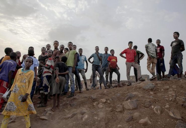 Ethiopian migrants stand on a hill at a slum in Dikhil, Djibouti, where they took shelter after entering the country, July 12, 2019, on their journey to Yemen. Most hope to eventually reach Saudi Arabia. Image by AP Photo / Nariman El-Mofty. Djibouti, 2019.
