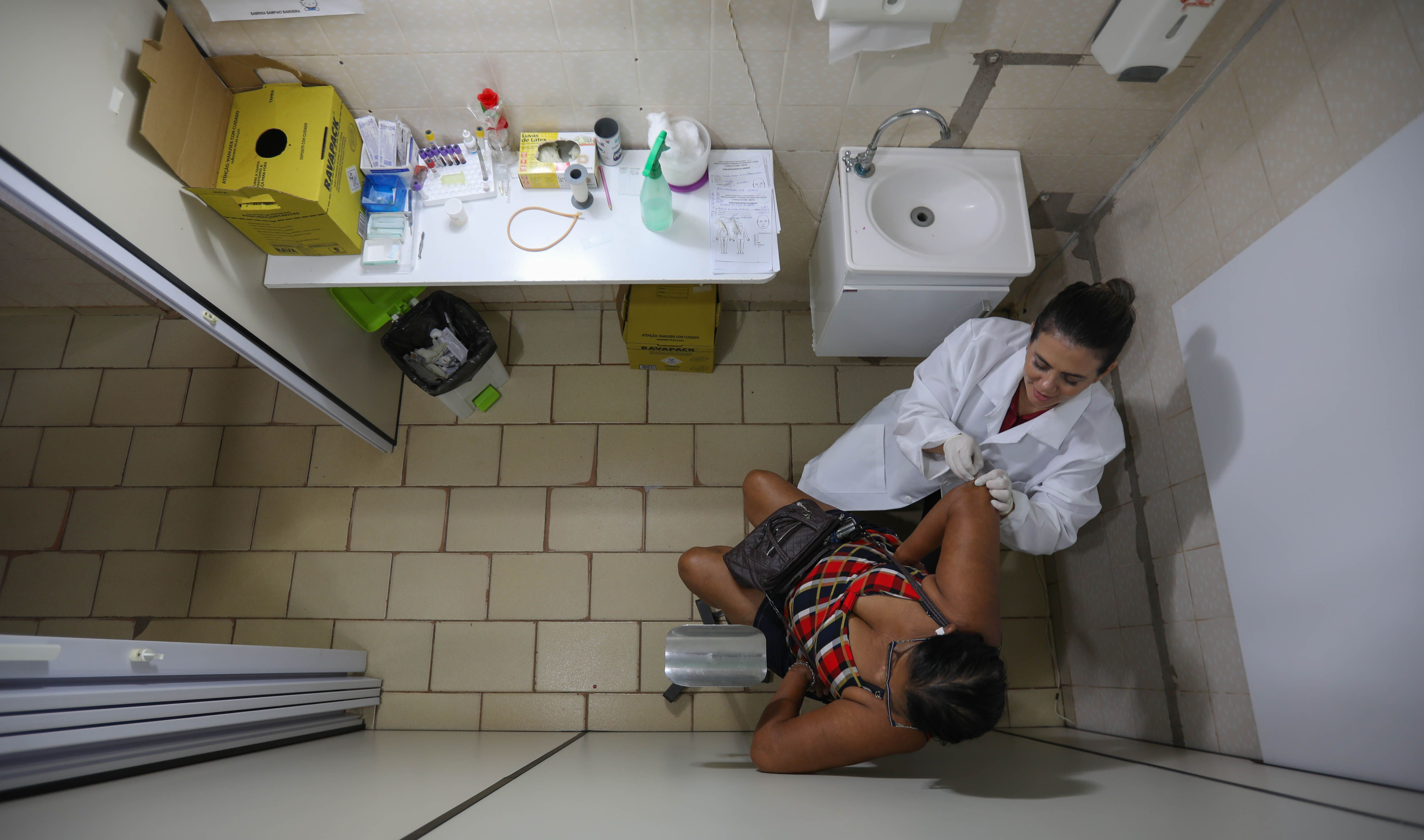 Erika Jorge, a member of the Laboratory of Dermatology-Immunology, takes skin samples from the elbow of a 60-year-old woman who had been exposed to leprosy. Image by Anton L. Delgado. Brazil, 2020.