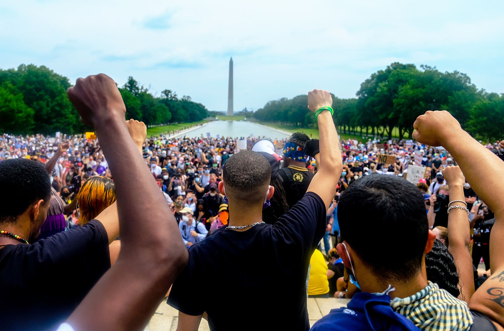 """Protesters hold the """"Black Power"""" fist during a rally at the Lincoln Memorial to protest against racism and police violence in downtown Washington, D.C. on June 6, 2020. Looking down the mall to the Washington Monument, this photo references the march on Washington of 1963 and MLK's famous """"I have a dream"""" speech. Image by Michael A. McCoy for the New York Times. United States, 2020."""