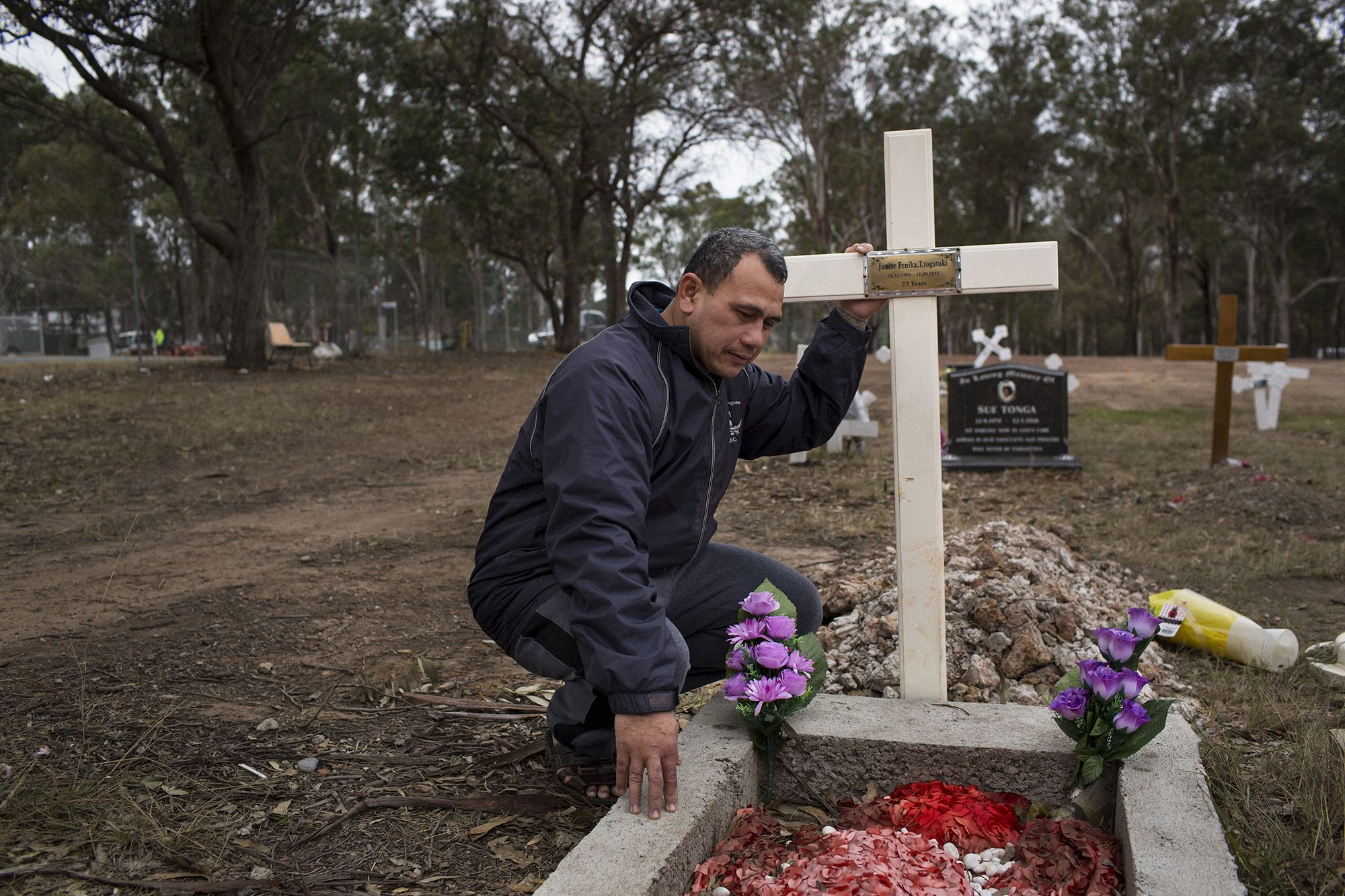 Vaea Togatuki, 48, visits the grave of his son, Junior, who died by suicide on September 11, 2015 while incarcerated in Goulburn's Correctional Center. Image by David Maurice Smith for The New York Times. Australia, 2018.