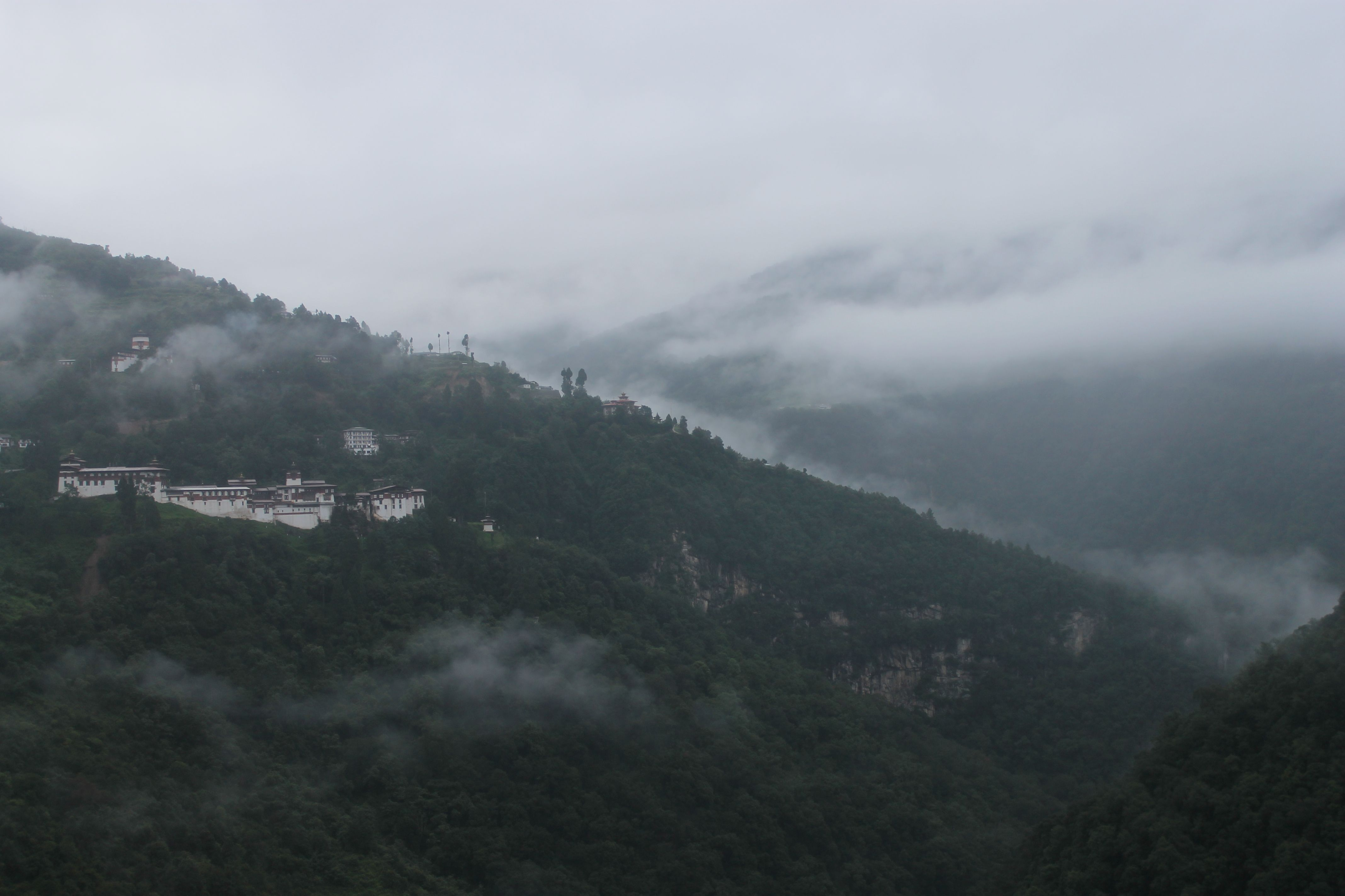 The Trongsa Dzong, or fortress, sits nestled among the trees in the early morning mist in the district of Trongsa. Image by Emma Johnson. Bhutan, 2019.