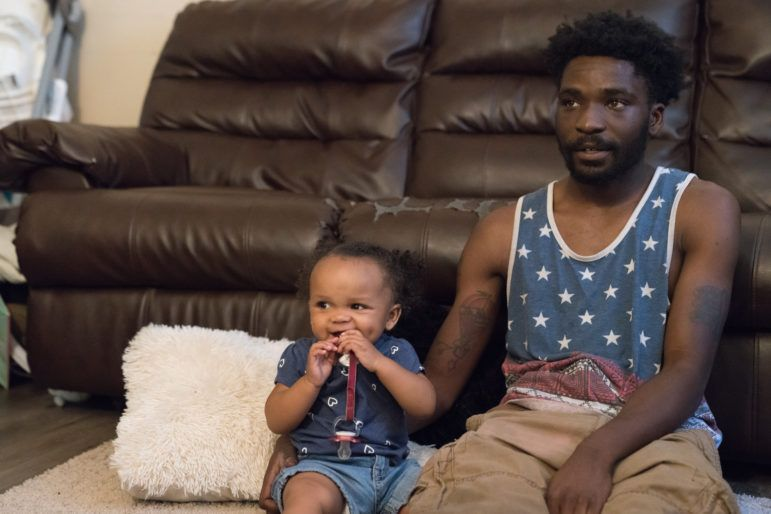 Theron Carson sits on the floor with his daughter watching cartoons. Carson was charged with trafficking marijuana and had $1,200 seized from his home after the police smelled weed coming from his Newburg apartment and conducted a search. Image by J. Tyler Franklin. United States, 2019.