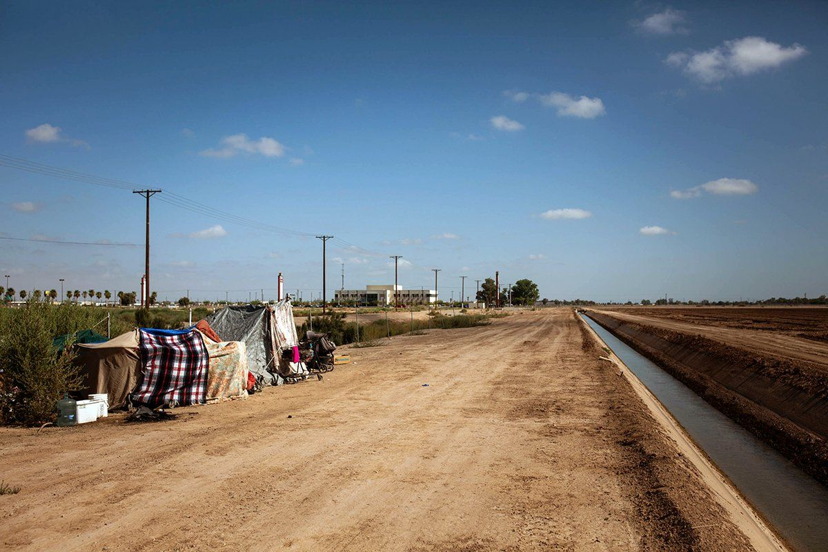 A homeless encampment near a canal in El Centro, Calif., as seen on July 24, 2020. As support services have dwindled amid the COVID-19 pandemic, some homeless people in Imperial County have resorted to bathing in irrigation canals. Homelessness looks different in different parts of the U.S., especially in rural agricultural regions such as Imperial County. Image by Anna Maria Barry-Jester/KHN. United States, 2020.