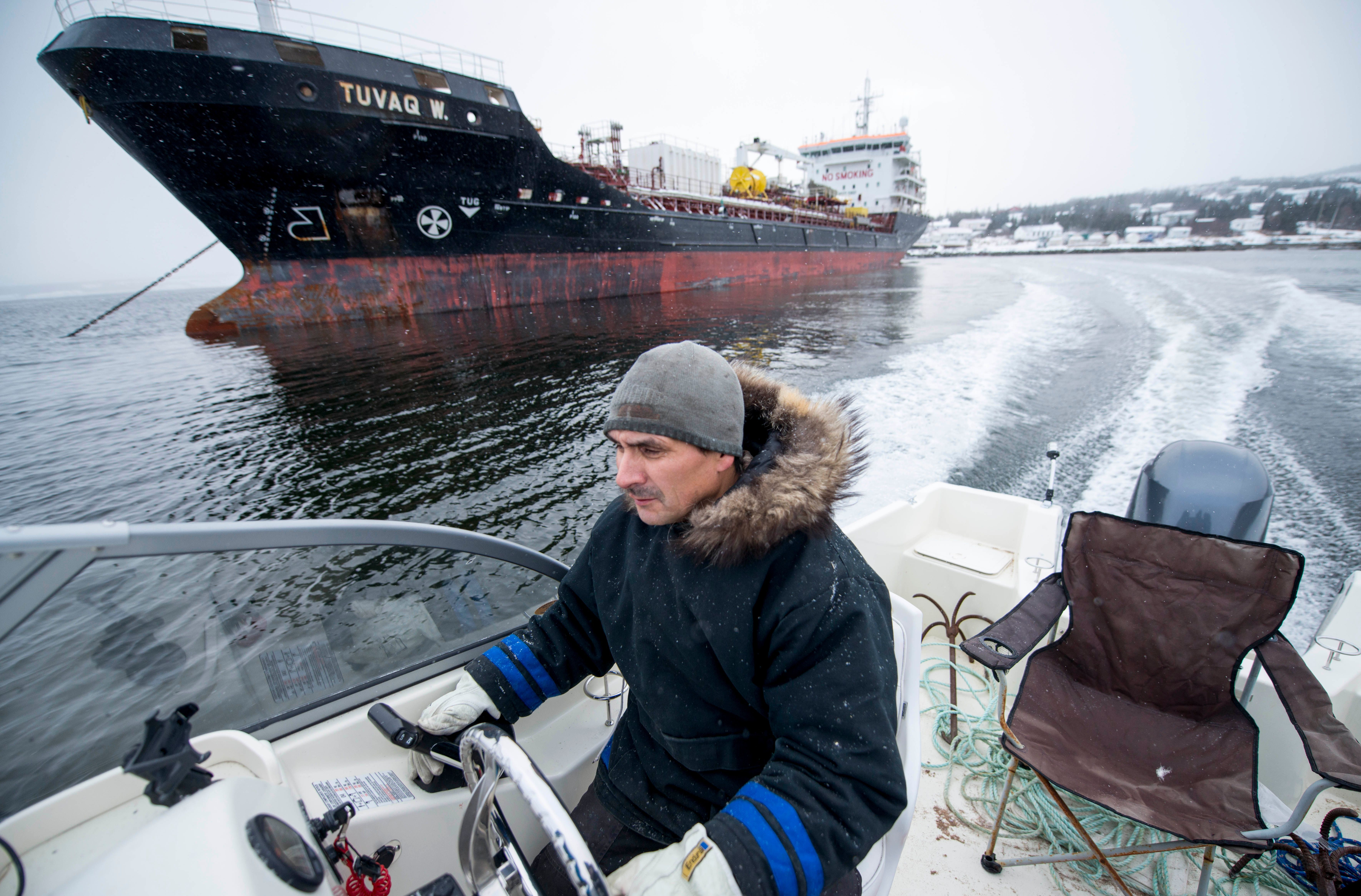 Karl Michelin speeds past a fuel tanker docked at the Rigolet dock for one of two yearly fuel drops on November 10, 2019. Image by Michael G. Seamans. Canada, 2019.