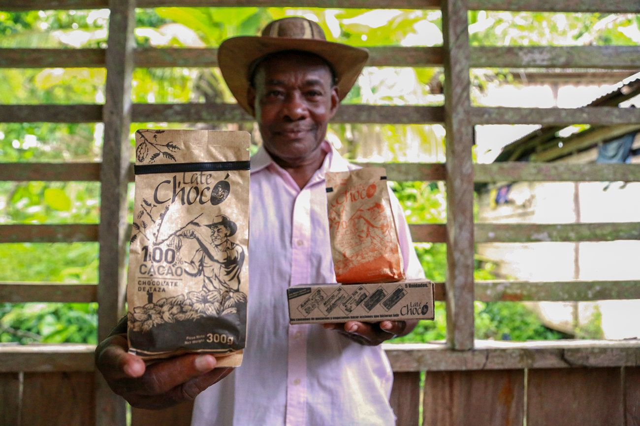José Palacios, a cacao farmer, holds the Late Chocó chocolate products produced by his son, Joel, in Bogotá. The package bears an illustration of his likeness. José Palacios lives in Colombia's western Chocó department, which is also a coca-growing region. Image by Verónica Zaragovia. Colombia, 2018.