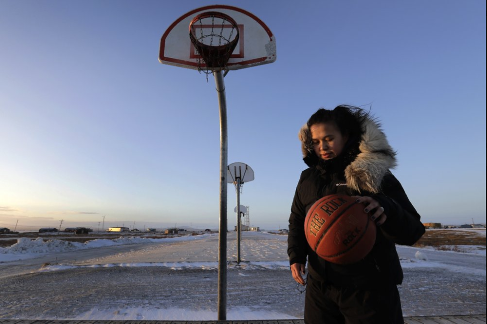 In this Feb. 17, 2019, photo, Deidre Levi carries her basketball as she walks to work in the Native Village of St. Michael, Alaska. Levi says she spoke up about being sexually assaulted because she wanted to be a role model for girls in Alaska. Image by Wong Maye-E/Associated Press. United States, 2019.