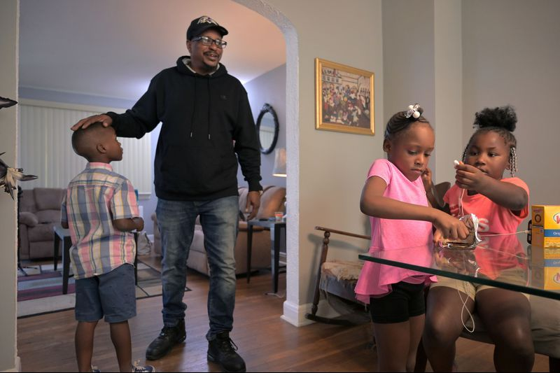 Cecil Burton, 54, is still paying down $60,000 in child support debt, much of which is owed to the state for welfare his children – now adults – received when they were young. Although he could not keep up with his child support orders, his kids say he was an involved dad who guided and nurtured them. During a family gathering in September, Burton visited with his grandchildren Kevin Ellis, 8, and Katelyn Ellis, 6, and his great-niece Saniyah Johnson, 6.  Image by Karl Merton Ferron / Baltimore Sun. United States, 2019.