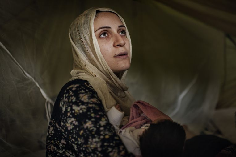 Taimaa Abazli, 24, holds her new baby Heln in their tent at the Karamalis camp in Thessaloniki. Image by Lynsey Addario for TIME. Greece, 2016.