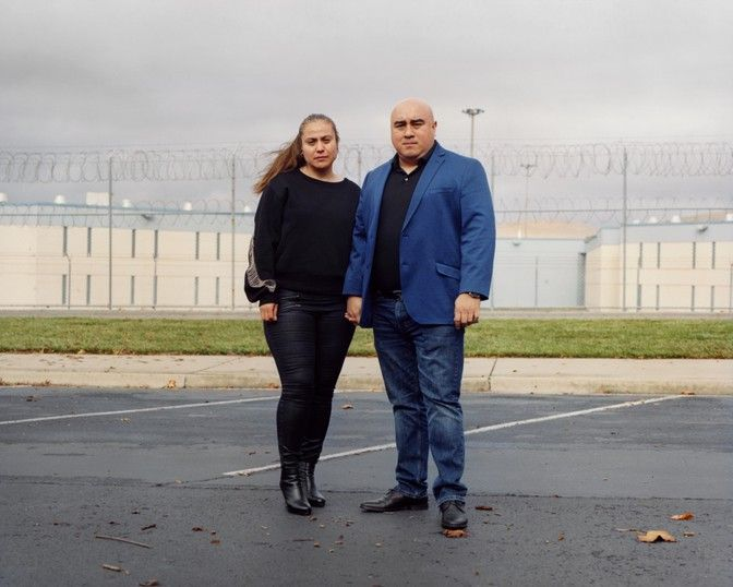 Gabby Covarrubias and Jose Jaime stand in front of Santa Rita Jail in Alameda County, California. Their son Christian Madrigal, who was suffering from a mental-health break, was found unconscious in his cell just hours after being admitted to the jail. Image by Carlos Chavarría/The Atlantic. United States, undated.