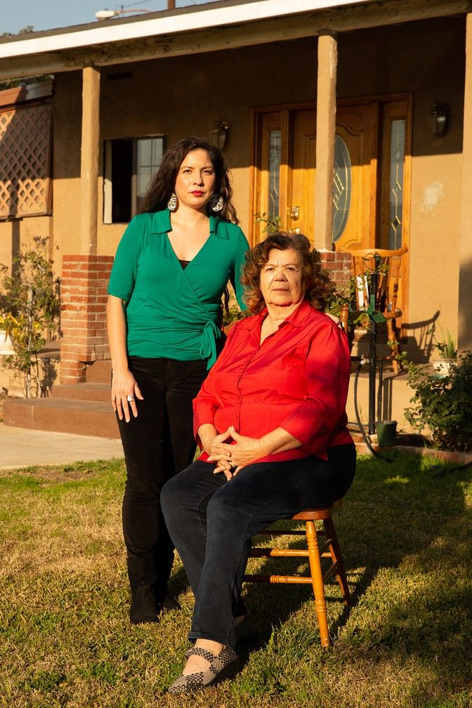 Diana Zuñiga and Antonietta Zuñiga stand in front of Antonietta's home in Pico Rivera in Los Angeles County, California, near the spot where Carlos Zuñiga was arrested and charged with residential arson for starting small fires in his backyard to keep warm. Image by Arlene Mejorado/The Atlantic. United States, undated.