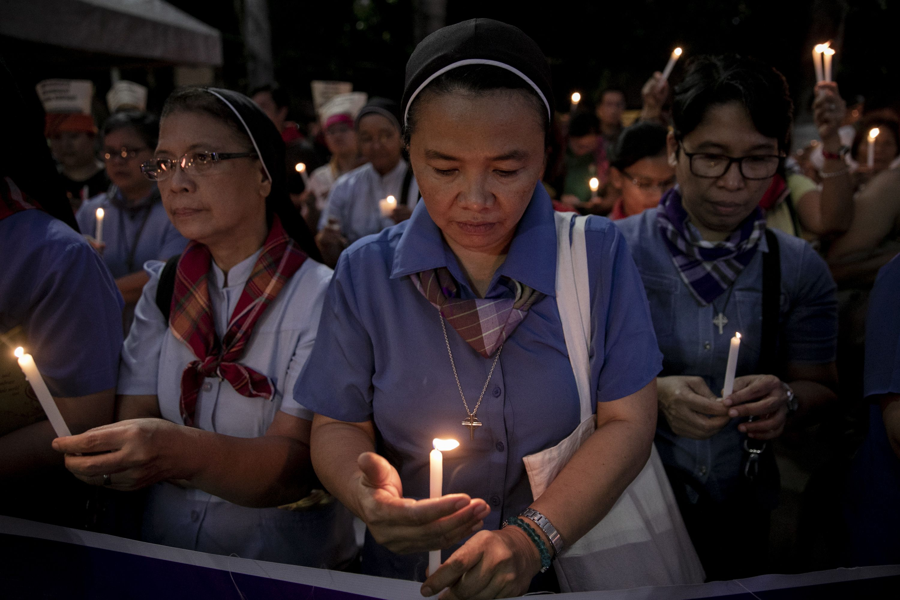 """Nuns light their candles during a demonstration calling for """"truth, justice, and peace"""" across Malate Church in Manila. Image by Eloisa Lopez. Philippines, 2019."""